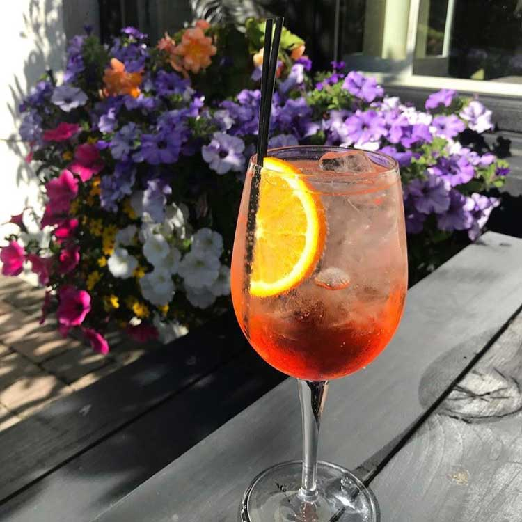 Aperol Spritz cocktail served on ice with a slice of orange