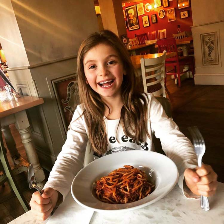 Smiling young girl with a large bowl of pasta